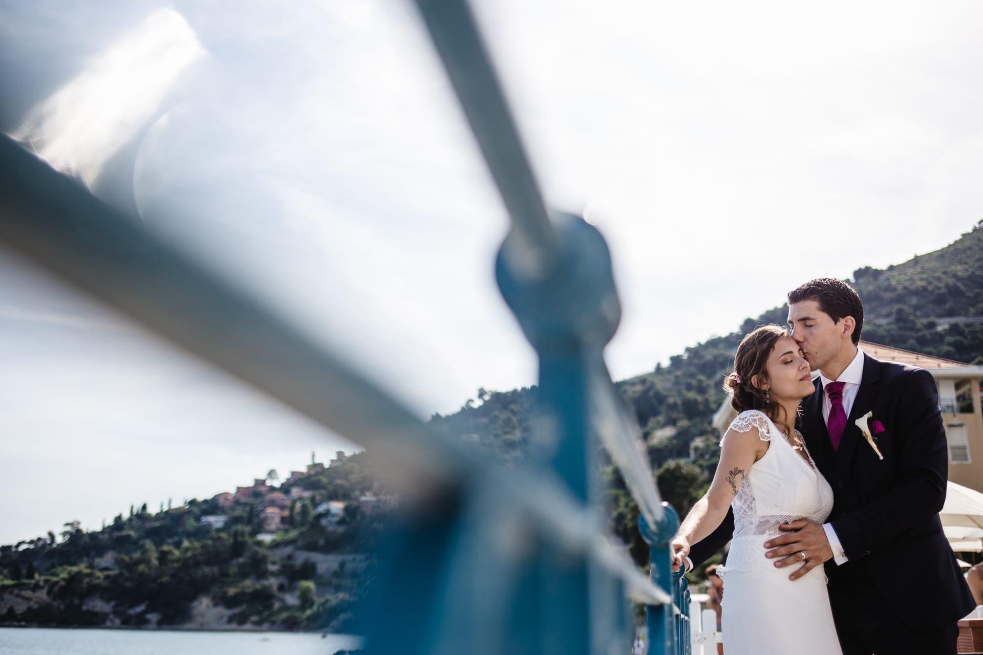 Marié embrasse la mariée sur le front, mariage à la mer